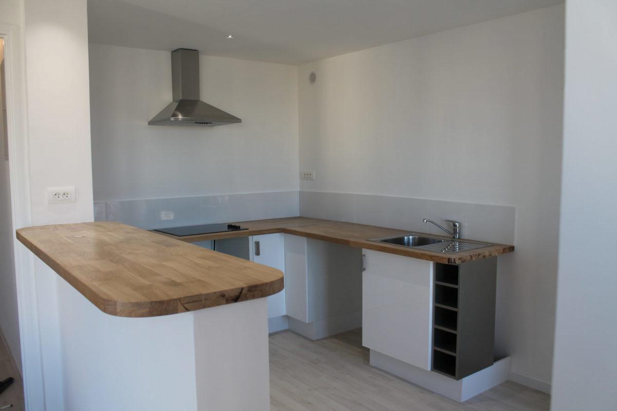 Installation d'une cuisine ouverte avec un comptoir qui donne sur la pièce à vivre. Plan de travail en bois.