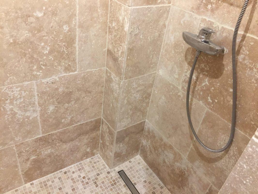 APRÈS Salle de douche revêtement travertin au sol et sur les murs