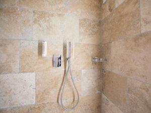 douche avec revetement en travertin au mur