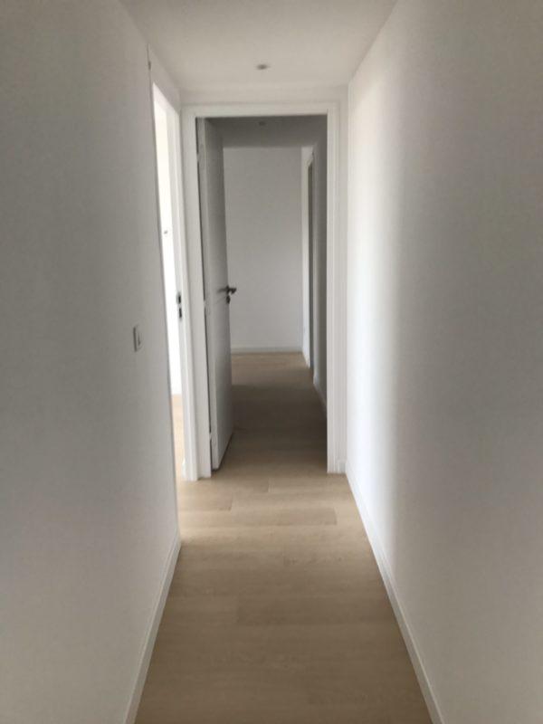 couloir renove, parquet stratifié au sol et murs blancs